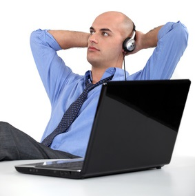 Office worker listening to music through headphones