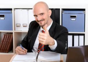 arbeitender Mann im Büro zeigt daumen hoch