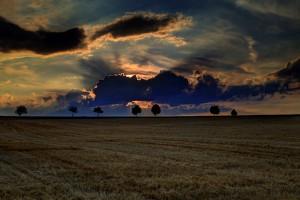 Zum Abend alle Felder abgeerntet, die Sonne geht unter und versteckt sich hinter Wolken.
