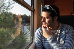 Mann betrachtet sein Spiegelbild im Zugabteil