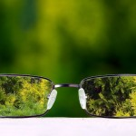 Eyeglasses placed on table with green nature background