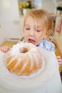Kleines Kind leckt heimlich den Zucker vom frischen Kuchen in der Küche